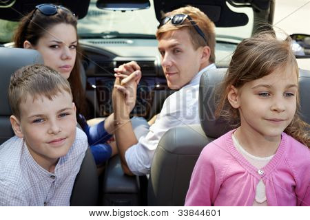 Young couple sits in cabriolet on front seats looking back, two children sit on  backseats, back view