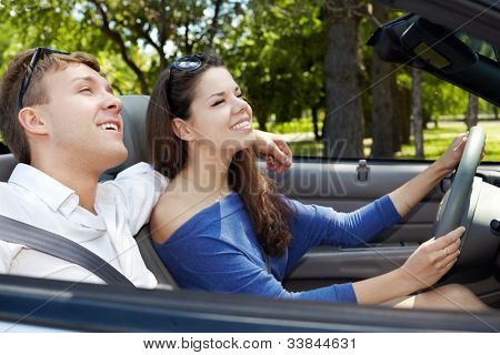 Young couple rides in a cabriolet, girl drives the car, focus on a boy face