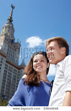 Young smiling couple stands embracing a little on background of blue sky near to Lomonosov Moscow State University main building.