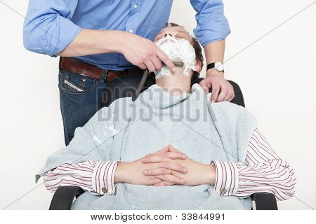 Man wrapped in towel being shaved with cut throat razor by barber over colored background