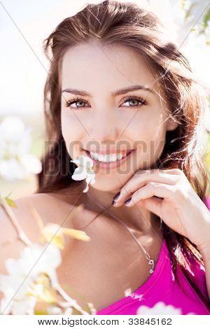 linda jovem morena com uma flor em seus dentes permanente perto a árvore de maçã em uma soma quente