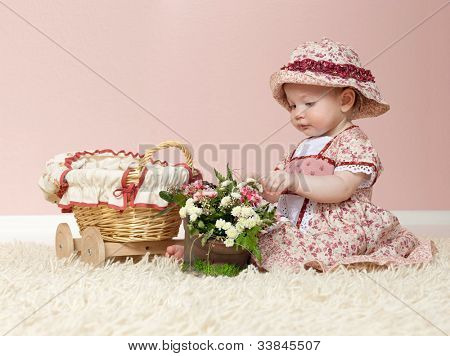 little child baby girl  indoors in baby room playing on the floor with flowers