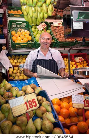 Smiling greengrocer at the market stall
