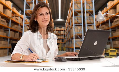Female administrative in a desk with a distribution warehouse in the background