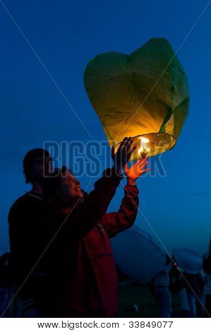 MOSCOW - JUNE 1: Young couple release floating lanterns during the First Day of Summer Festival, on June 1, 2012 in Moscow. During the festival flew more than 1,000 lamps.