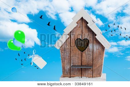 Birdhouse in the sky with floating balloons