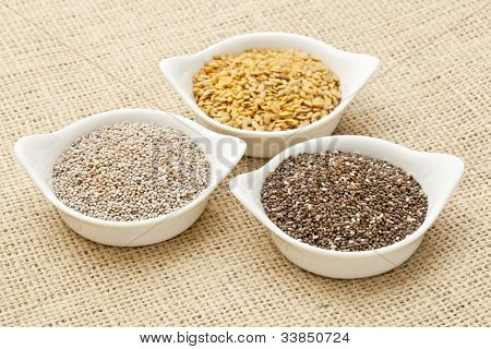 white and brown chia and golden flax seed in white ceramic bowls against burlap canvas