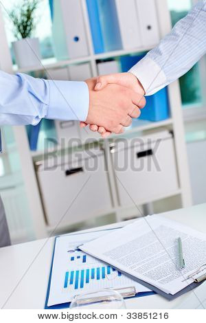 Photo of handshake of business partners after striking deal on background of documents