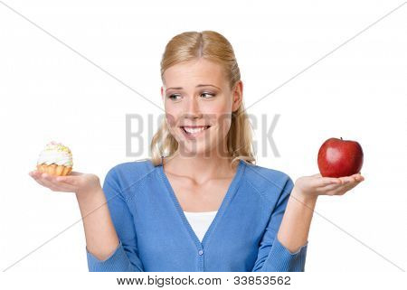 Mulher atraente faz uma escolha difícil entre o bolo e apple, isolado