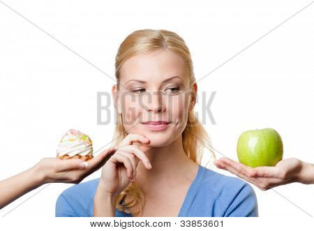 Beautiful woman makes a tough choice between cake and apple, isolated on white