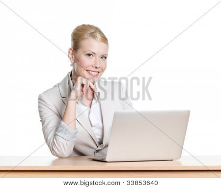 Young business woman sitting at a desk with laptop, looking at the camera