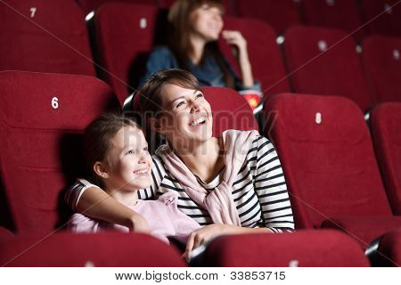 Loughing mother and daughter at the cinema watching a movie