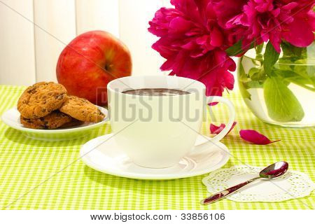cup hot chocolate, apple, cookies and flowers on table in cafe