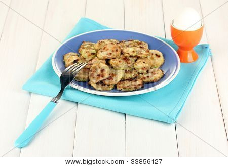 calabaza asada en un recipiente azul con el huevo para desayunar en primer plano de la mesa de madera blanca
