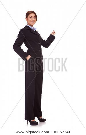 full body picture of a smiling business woman presenting something on the back with hand holding marker. Isolated over white background