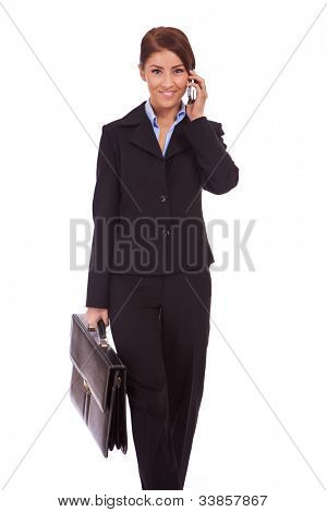 young business woman with briefcase talk on the phone and walking towards the camera