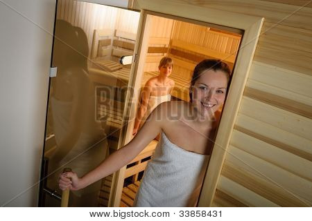 Sweaty young woman standing in front of the sauna