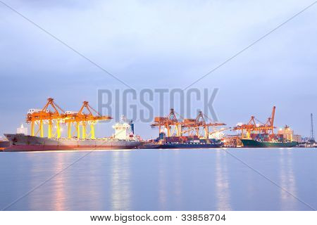 Big Container Cargo freight ship with working crane in shipyard at night for Logistic Import Export background