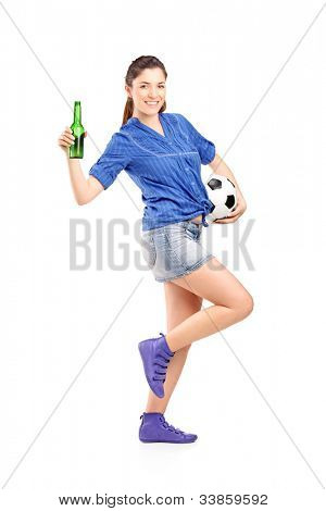 Full length portrait of a happy female fan holding a football and beer bottle isolated on white background