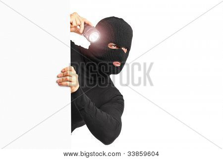 A thief with robbery mask holding a flashlight behind a white panel isolated on white background