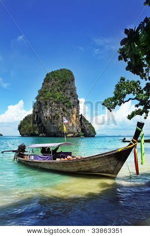 Seascape with exotic island and long tail boat in Thailand