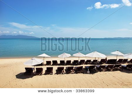 Beautiful tropical beach with white sunshades