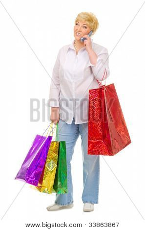 Senior woman with mobile phone and bags isolated