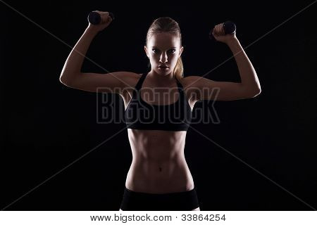 Sexy woman doing exercises with dumbells over black background