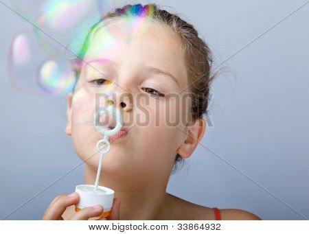 Portrait of lovely little girl blowing soap bubbles