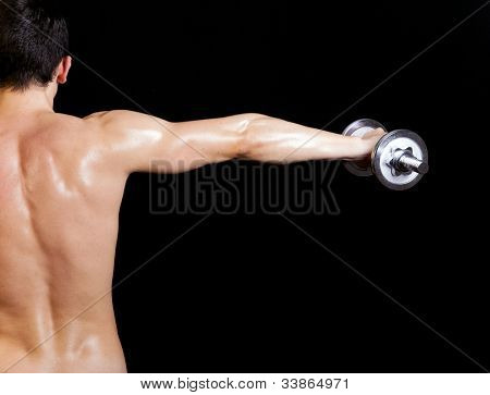 Back view of a young male doing exercise with dumbbells against dark background