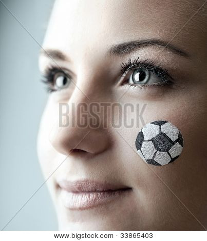 Closeup portrait of a happy football fan, painted face of a pretty woman watching ball competition, young female team supporter enjoying sport game, cute girl smiling, shallow DOF