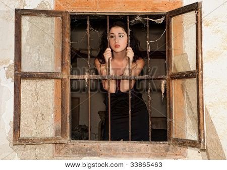 Staring woman looking out of a window of a derelict prison