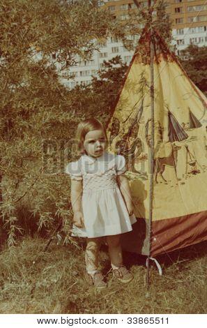 Vintage photo of  little girl and toy wigwam (early eighties)