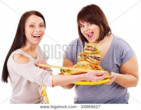 Woman holding fast food and measuring tape. Concept.