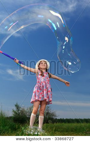 Happy girl is playing with big bubbles in a park.
