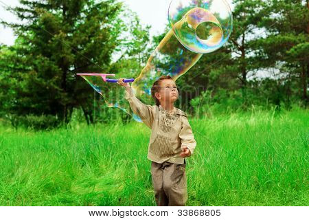Portrait of a cute little boy playing with big bubbles outdoor.