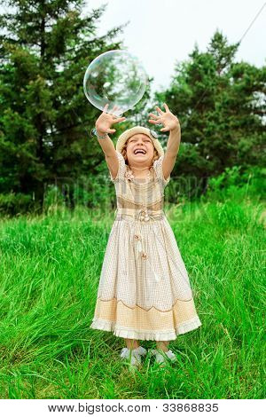 Pretty little girl is playing with big bubbles in a park.