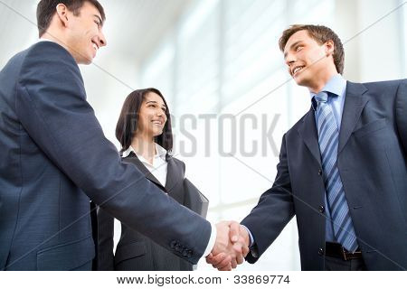 Business people shaking hands in modern office