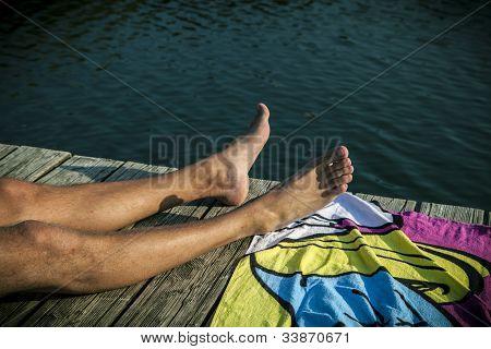 Mann auf Laufplanke liegen, Relaxen im Sommer mit einem Bade-Handtuch