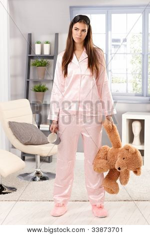 Grumpy sleepy woman in trendy pyjama standing with coffee mug and teddy bear handheld in living room, looking annoyed.