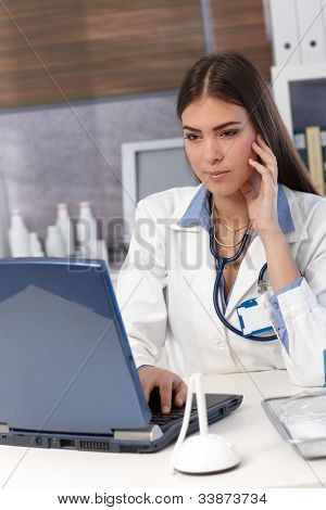 Young female doctor working on laptop computer at office desk.