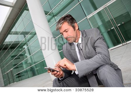 Businessman using mobile phone while seated in stairs
