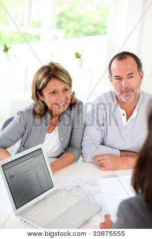 Pareja Senior listo para comprar el nuevo contrato de lectura de la casa