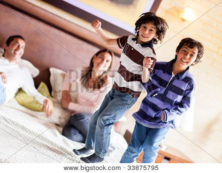 Happy kids jumping on the parents bed and having fun