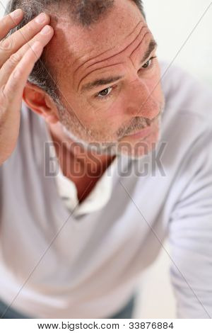 Senior man looking at his hair in mirror