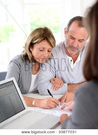 Senior couple signing financial contract