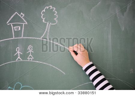 Childs hand drawing on a blackboard