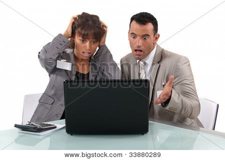 Two business people shocked by laptop