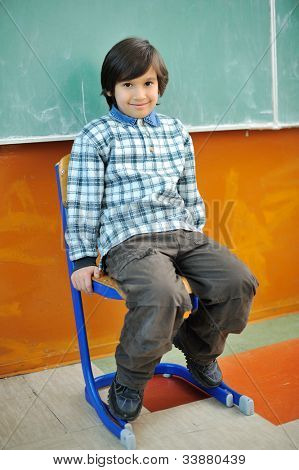 Cute little boy sitting in chair in front of blackboard