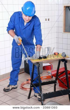 Plumber sawing grey plastic pipe